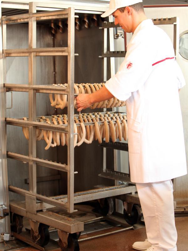 Fleischer bei Bratwurstproduktion